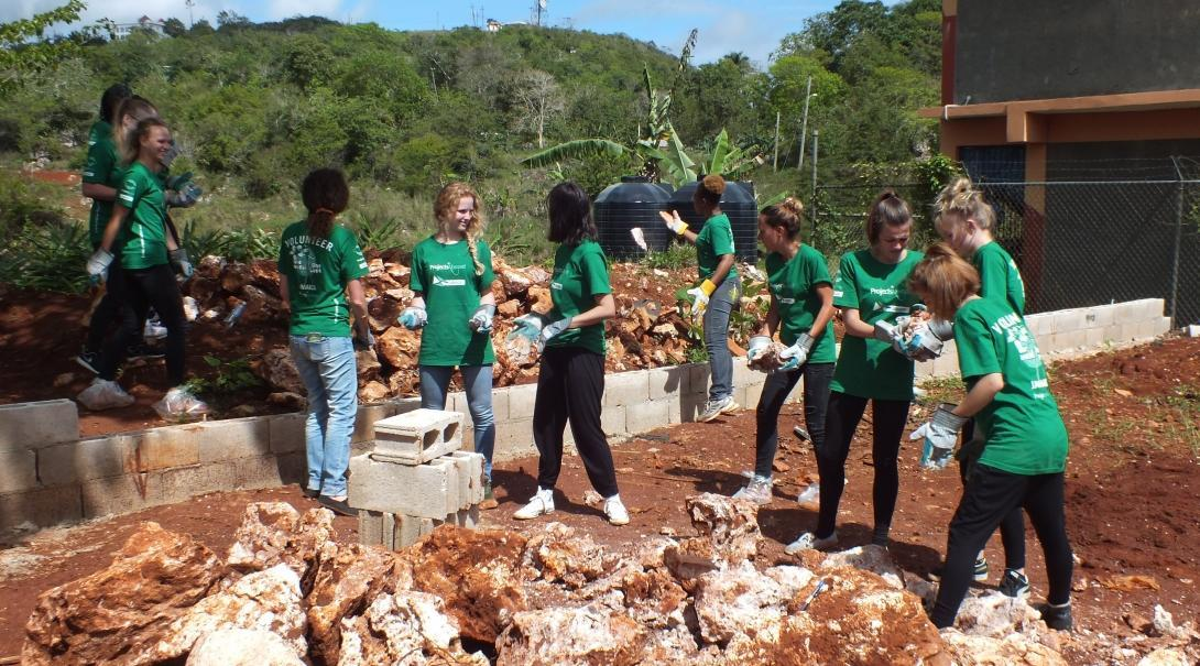 A group doing building volunteer work in Jamaica help clear ground at a school to construct a playground.